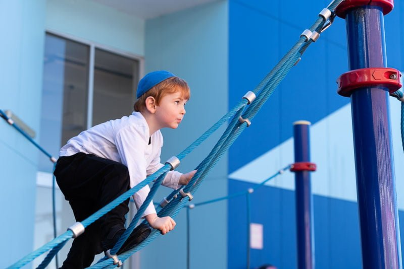 boy climbing on monkey bars at school