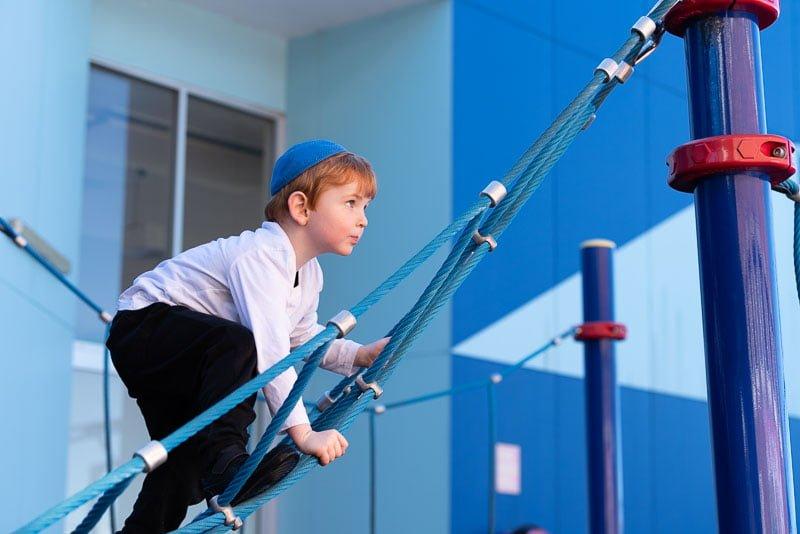 boy climbing on monkey bars at school
