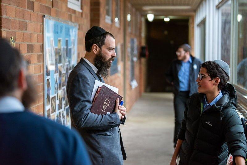 teacher admonishing student in corridor at school