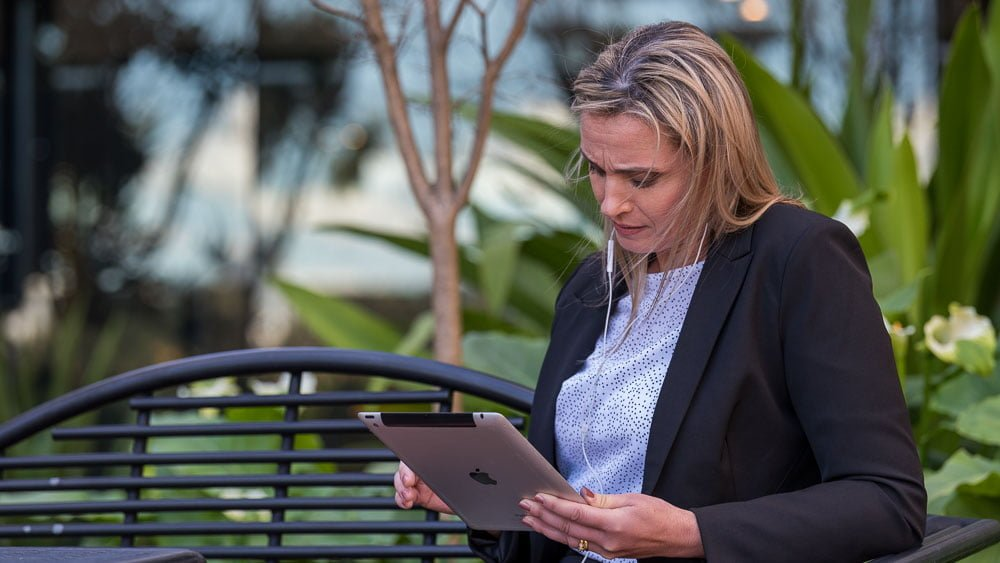 on location portrait of a woman on park bench checking her iPad